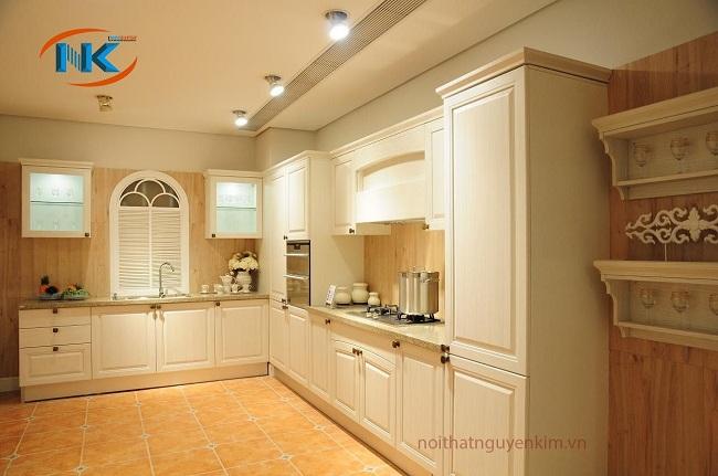 Mẫu tủ bếp gỗ sồi nga sơn trắng dáng chữ L theo phong cách cổ điển. Đường nét uốn lượn, chạm khắc khá tinh tế