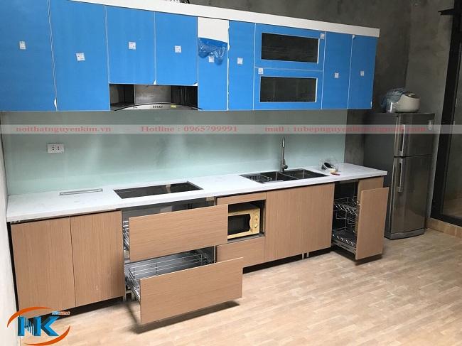 Bộ tủ bếp acrylic đã thi công xong, cánh tủ acrylic màu trắng chưa bóc lớp giấy dán chống trầy xước khi vận chuyển