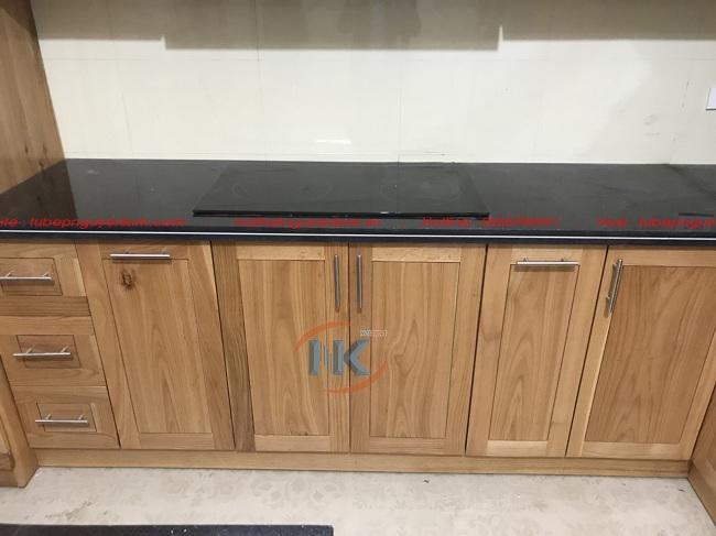 Hình ảnh ghi lại một phần tủ bếp dưới khi hoàn thiện với mặt bàn bếp đá kim sa đen làm điểm nhấn