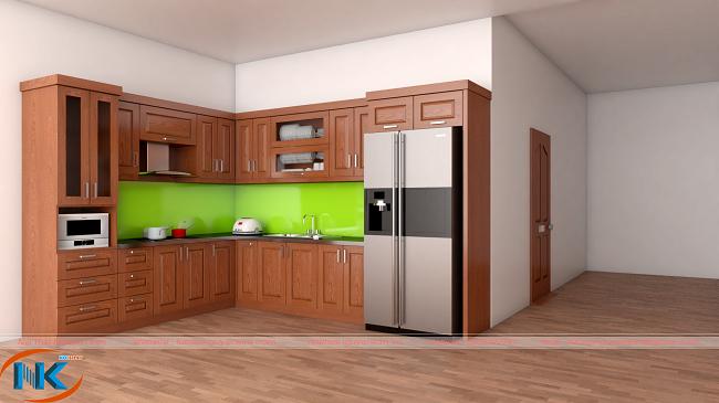 Thiết kế tủ bếp gỗ xoan đào chữ L nổi bật bởi màu cánh gián đậm cũng như màu xanh của kính ốp bếp.