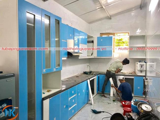 Bộ tủ bếp acrylic chữ L màu trắng bóng gương được thi công tương đối hoàn thành